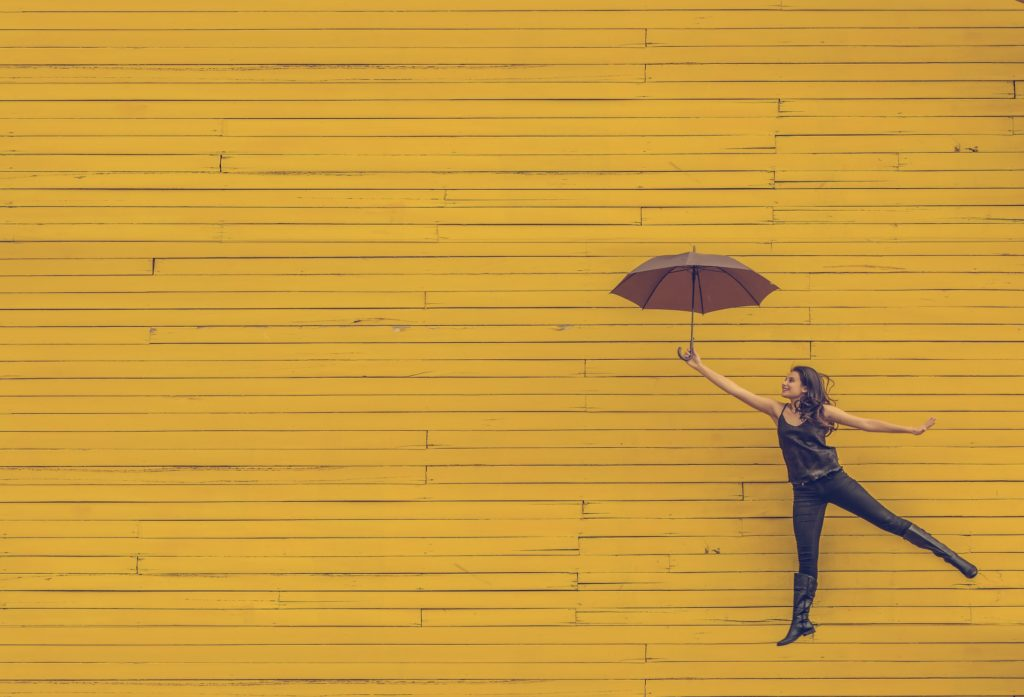 傘を持って飛ぶ女性